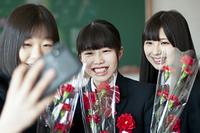 教室で自撮りをする女子学生