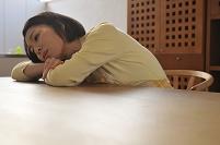 テーブルに伏せてぼんやりする日本人女性
