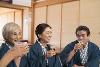 ビールで乾杯す浴衣と羽織の中高年夫婦と姑