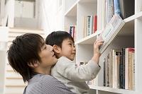 父に抱えられて本をとる息子