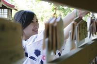 絵馬をかける浴衣の日本人女性