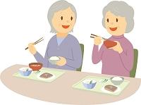 老人ホームで食事を楽しむシニア