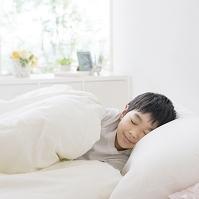 ベッドで眠る日本人の男の子