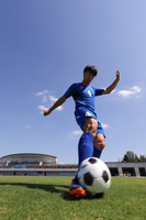 ボールを蹴るするサッカー選手