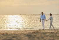 ビーチを散歩する日本人シニア夫婦