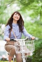 並木道で自転車に乗る日本人女性