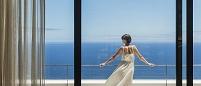 バルコニーから海を眺める外国人女性