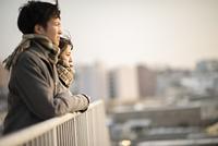 遠くを眺める高校生のカップル