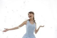 舞う羽と水色のウエディングドレス姿の日本人女性