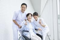 車椅子に乗るシニア女性と介護士の男女