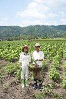 畑の中で収穫した作物を持つ20代カップル