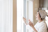 窓掃除をする年配の日本人女性