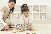 木のおもちゃで遊ぶ女の子とお母さん
