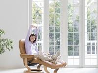 椅子に座り背伸びをする女性
