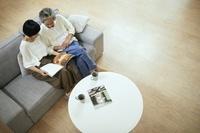 リビングで雑誌を読む日本人中年夫婦
