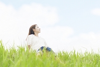 青空と土手に座る若い日本人女性の横顔