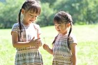 白ツメ草の指輪をはめるお姉ちゃんとそれを見つめる妹