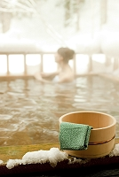 温泉の桶と手ぬぐいと入浴する女性