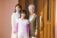 玄関前に立つ日本人の女性三世代親子