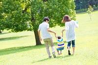 公園を歩く日本人三人家族の後ろ姿
