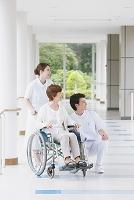 廊下にいる車椅子のシニア女性と若い看護師