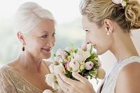 ブーケを持って微笑む花嫁と母