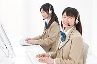 インカムをつけてパソコンをする女子高生