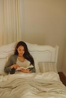 ベッドで読書する日本人女性