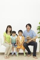 ソファーに座る日本人家族と犬