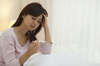 体温計で熱を計る体調不良の日本人女性