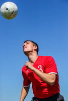 ヘディングする外国人サッカー選手