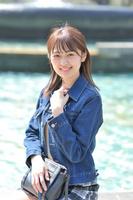 日比谷公園のふちに腰かけて微笑む日本人女性
