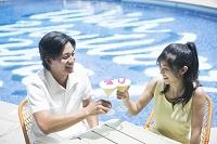 プールでカクテルを飲む20代男女