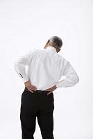 腰痛で腰に手をやる中高年日本人男性