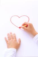 クレヨンでハートの絵を描く子供の手