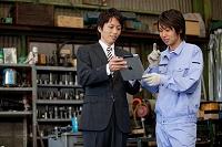 iPadを見る作業員と営業マン