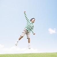 草原でジャンプする日本人の男の子