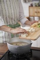 味噌汁の具材を鍋に入れる女性