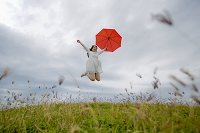 草原で傘を持ってジャンプをする日本人女性