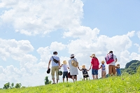 夏の土手を歩く行楽の2家族