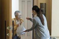 ホームヘルパーから料理を受け取るシニアの日本人女性