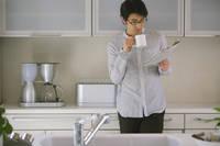キッチンで新聞を読む男性