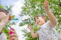 公園でシャボン玉を吹く母親と娘