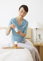 ベッドでサプリメントを飲むシニアの女性
