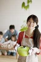 鍋を持ち微笑む母親