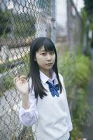 フェンスに寄りかかる女子高生