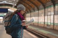 駅で地図を見る若い女性