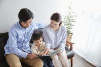 ソファで絵本を読む家族