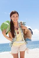 海岸で鞄と帽子を持っている笑顔の日本人女性