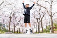 桜並木で手を広げジャンプする男の子